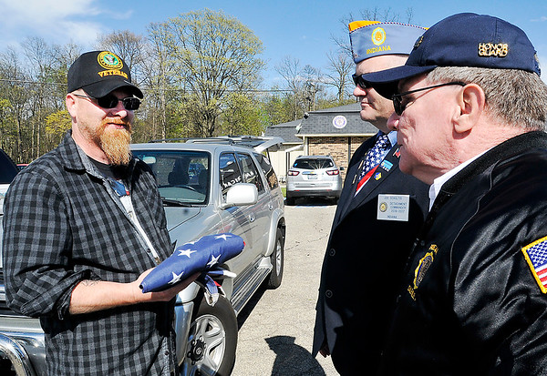 John P. Cleary |  The Herald Bulletin<br /> The new post commander for American Legion Post 408 Chris Brenneman, left, receives the old American flag after it was retired during a reopening celebration for the post from Honor Guard member Gary Benefiel, right as American Legion Indiana detachment commander Joe Schultis looks on.