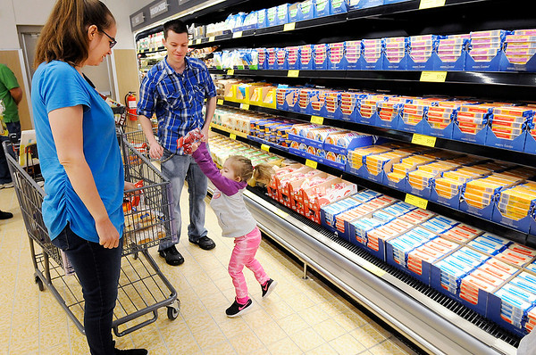 Don Knight   The Herald Bulletin<br /> Tori and Josh Peterson look on as their daughter Loralye puts some cheese in their shopping cart during ALDI's reopening on Thursday.