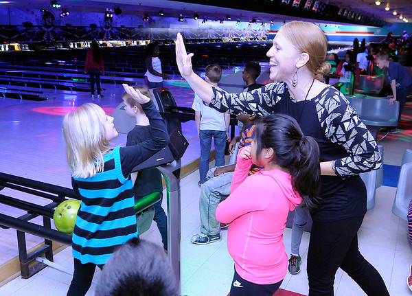 Don Knight | The Herald Bulletin<br /> Amy Wilkins gives her student Chloe Wallace a high five after Wallace rolled a strike as Anderson Elementary students went bowling at Championship Lanes on Friday.