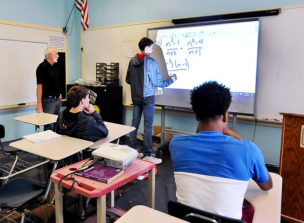 John P. Cleary |  The Herald Bulletin<br /> Liberty Christian 9th grader Cade McCord works a problem on the board as teacher Jim Hostetler looks on in his Algebra I class. School officials say the 83-year-old facility has outlived its usefulness and has no room for expansion.
