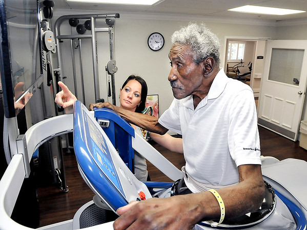 John P. Cleary |  The Herald Bulletin<br /> Olivia Rhea, phyical therapist assistant, helps Gene Wilson watch his feet movement in the monitor as he uses the AlterG anti-gravity treadmill for his therapy at Providence Anderson.
