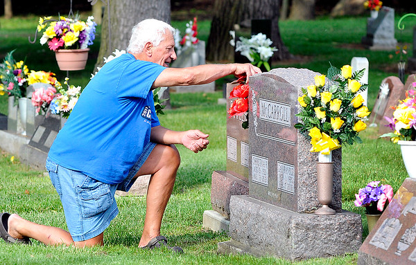 John P. Cleary |  The Herald Bulletin<br /> Dwain McCarroll, of Middletown, cleans around and places flowers on his parents grave in Maplewood Cemetery Friday evening for Memorial Day.
