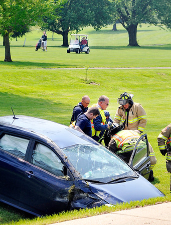 John P. Cleary |  The Herald Bulletin<br /> As golfers play up the 15th fairway at Grandview Golf Course Anderson Fire Department rescue and medic personnel tend to a injured woman who lost control of her vehicle and crashed down the embankment onto the golf course along Raible Ave. Wednesday.