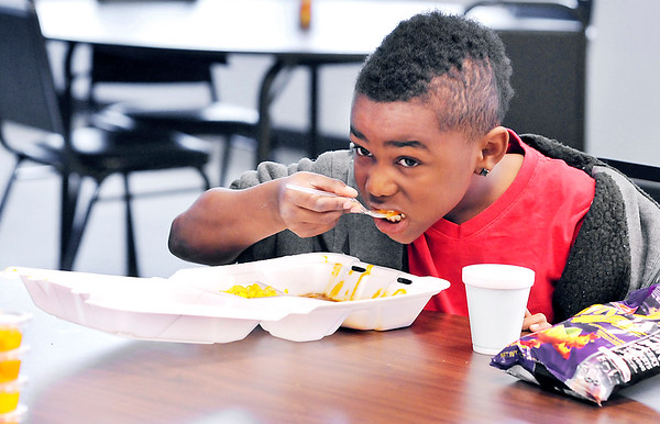 John P. Cleary |  The Herald Bulletin<br /> Daurell Boulware, 8, eats up his ravioli as he enjoys the after-school meal offered at the Trustee Girls and Boys Club Tuesday afternoon.