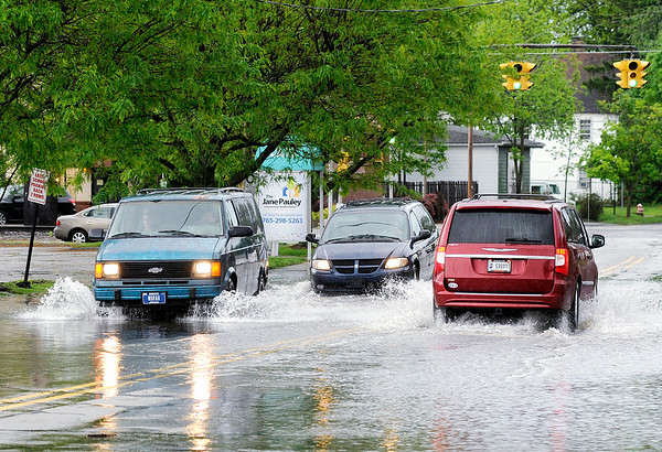 Don Knight | The Herald Bulletin<br /> Cars drive through standing water on Nichol Avenue after heavy rain moved through Friday afternoon. More rain and storms are in the forecast for the weekend.