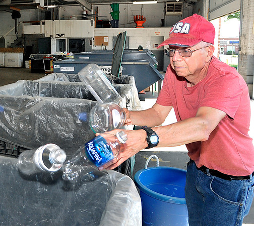 John P. Cleary |  The Herald Bulletin<br /> Denny Beltz, of Anderson, tosses a handful of #1 plastic bottles into the bin as he sorts out his items for recycling at the Madison County Recycling Center Tuesday morning.