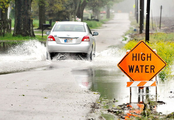 John P. Cleary    The Herald Bulletin<br /> This vehicle drives through the standing water that is covering this section of County Road 50 West south of CR375 North Thursday as the rains from the past several days have caused high water on several areas of roadways around the county.