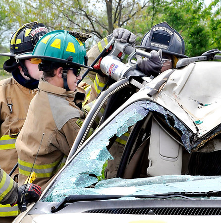 """John P. Cleary    The Herald Bulletin<br /> Students from Anderson Community Schools' D26 Career Center fire and rescue class use the jaws-of-life to extricate """"accident victims"""" as they participate in a mock vehicle accident training exercise Wednesday as part of their schooling."""