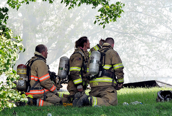 John P. Cleary    The Herald Bulletin<br /> These firefighters take a break after battling a house fire in the 1000 block of Indiana 38 Thursday afternoon.