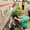 Don Knight | The Herald Bulletin<br /> From left, Lillian Scott and Liliana Hernandez, Girl Scouts from Troop 3601, plant a shrub in front of the East Elementary sign on U.S. 36 on Tuesday. The troop wanted to use some of the proceeds from their cookie sales to beautify the school and chose to landscape around the school's sign with about $400 worth of plants, or about the equivalent of 770 boxes of cookies sold. The girls had help from landscape designer Tammy Doty-Davis who is also one of the troops leaders.