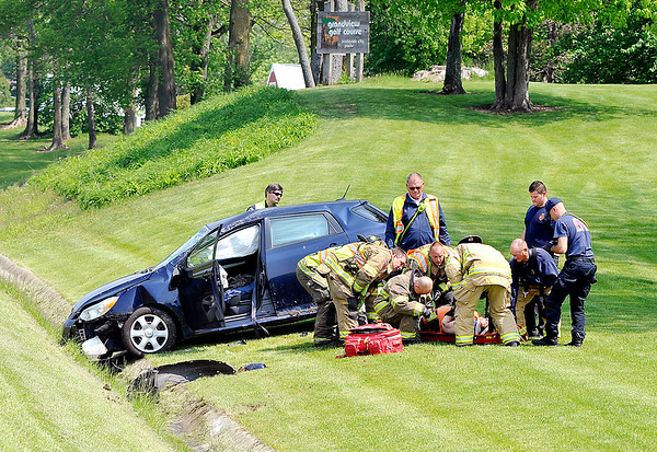 John P. Cleary |  The Herald Bulletin<br /> Anderson Fire Department rescue and medic personnel tend to a injured woman who lost control of her vehicle and crashed down the embankment onto Grandview Golf Course along Raible Ave. Wednesday.
