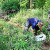 John P. Cleary |  The Herald Bulletin<br /> Fire department and hazmat personnel put down booms along the small creek to help stop the seeds and chemicals from making their way into Fall Creek which is a short distance away from the spill.