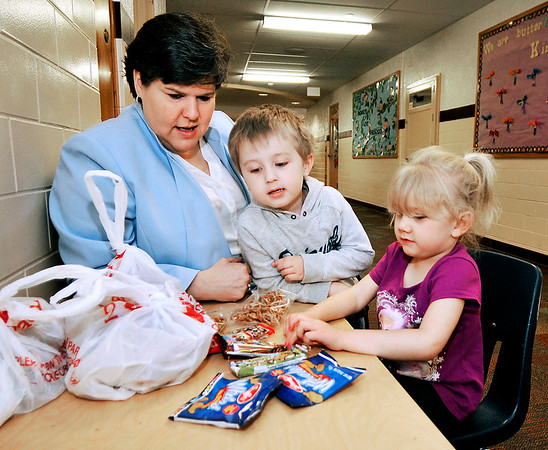 John P. Cleary |  The Herald Bulletin<br /> Alexandria School Superintendent Melissa Brisco and pre-schoolers Karter Scott and Mykenzee Weaver check out the school's Buddy Bags.