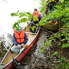 Don Knight | The Herald Bulletin<br /> Bob Whited picks up a discarded smokeless tobacco can during cleanup<br /> efforts around Shadyside Park on Saturday. Michael Kippen was in the canoe with Whited and Bill Evans was helping from the shore.