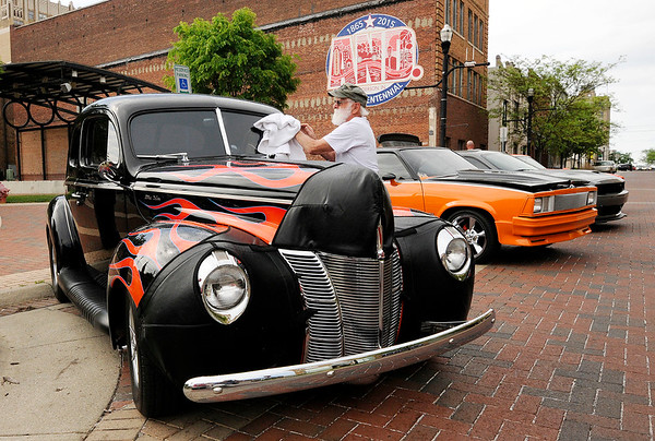 Don Knight | The Herald Bulletin<br /> Sid Hiatt wipes rain drops of his 1940 Ford Coupe that he has owned for 51 years after a light rain on Tuesday. Hiatt was participating in the Anderson Tuesday Night Cruise In held at the Dickmann Town Center park.