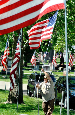 John P. Cleary   The Herald Bulletin Maplewood Cemetery employee Keith Sherman puts up one of approximately 260 American flags along the lanes of the cemetery Wednesday as the staff prepares for the Memorial Day holiday weekend.