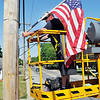 John P. Cleary | The Herald Bulletin<br /> Town of Chesterfield employee Trampas Fetters moves down Main Street in a lift Friday as he puts up American flags for the Memorial Day holiday.