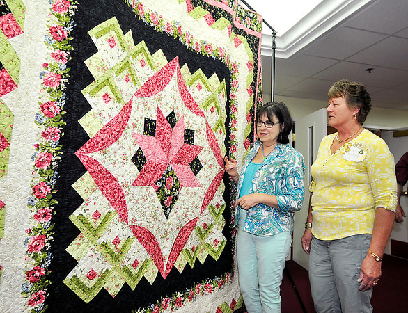John P. Cleary   The Herald Bulletin<br /> Nan Hodge and Nancy Muething, co-chairs of the Redbud Quilt Guild's biennial quilt show, admire this year's quilt that will be raffled off at the event.