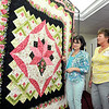 John P. Cleary | The Herald Bulletin<br /> Nan Hodge and Nancy Muething, co-chairs of the Redbud Quilt Guild's biennial quilt show, admire this year's quilt that will be raffled off at the event.