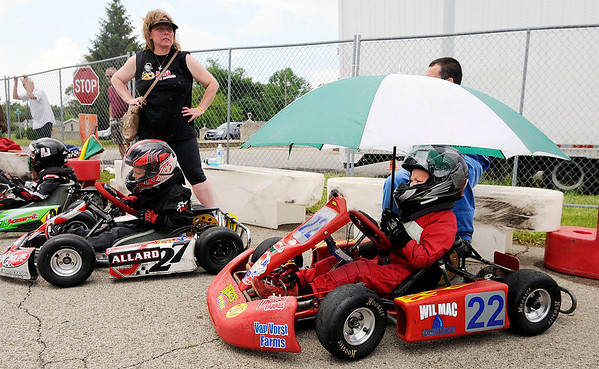 Don Knight   The Herald Bulletin<br /> Grahm Kriser stays dry under an umbrella while waiting for the Kids Kart feature to start during the 24th annual Mayor's Cup Grand Prix at Mounds Mall on Saturday.