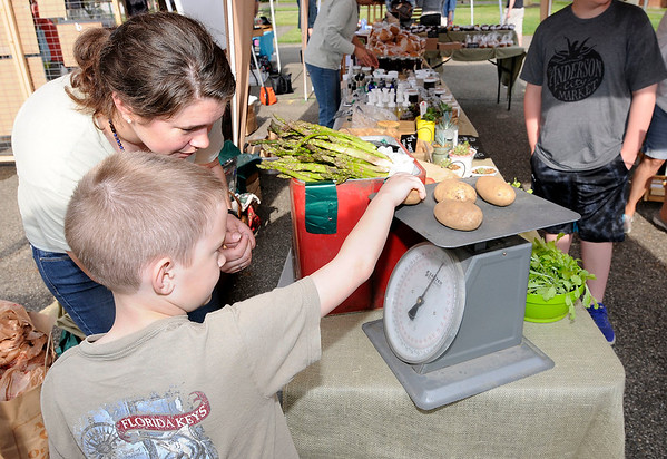 Don Knight   The Herald Bulletin<br /> Kayleigh Jarrell looks on as Asa Butler weighs a pound of potatoes at the Asparagus Annie's booth at the Anderson City Market opened at Park Place Community Center on Saturday.
