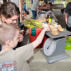 Don Knight | The Herald Bulletin<br /> Kayleigh Jarrell looks on as Asa Butler weighs a pound of potatoes at the Asparagus Annie's booth at the Anderson City Market opened at Park Place Community Center on Saturday.
