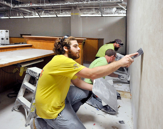 John P. Cleary | The Herald Bulletin<br /> Aaron Slack, foreground, Mike Turner, and Geoff Pierce, from Dennis Mallernee Painting & Plastering, work on a wall in Circuit Court 4 on the third floor of the Madison County Government Center Wednesday. The remodeling and asbestos removal work at the building is over budget by a minimum of $623,500.