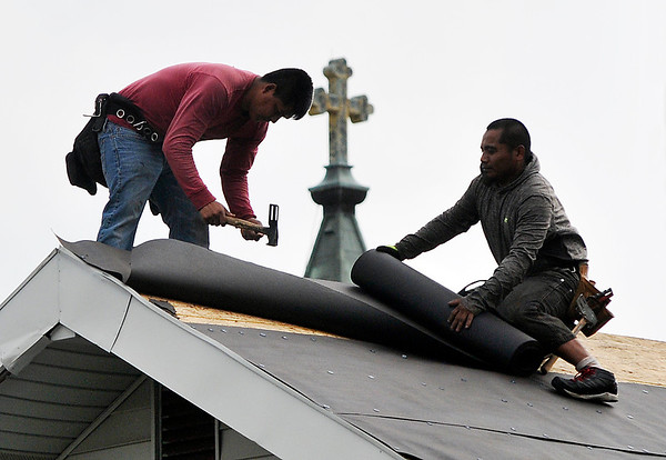 John P. Cleary   The Herald Bulletin<br /> These workers frame the large cross on the top of the steeple of St. Mary's Catholic Church as they put on a new roof on a house along Central Avenue.