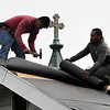 John P. Cleary | The Herald Bulletin<br /> These workers frame the large cross on the top of the steeple of St. Mary's Catholic Church as they put on a new roof on a house along Central Avenue.