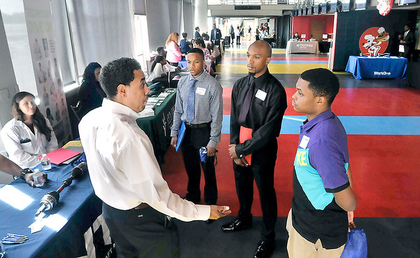 John P. Cleary   The Herald Bulletin<br /> Tyrone Thomas, manufacturing senior manager NTN Driveshaft Anderson, talks with Andrew Nunn, Chris Nunn, and Kris Perry at the Madison County Black Chamber of Commerce Job Fair Thursday held at Hoosier Park Racing & Casino.