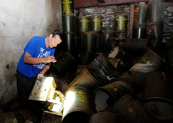 Don Knight | The Herald Bulletin<br /> Tim Bowers looks at a tin of crackers in a former fallout shelter in Anderson. The green cans in the background served a dual purpose, drinking water storage and containment of human waste after all the water had been consumed.