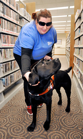 John P. Cleary | The Herald Bulletin<br /> Kassie Lemons gives her guide dog Kingsley praise as they navigate the auto-book section of the Anderson Public Library recently.