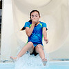 Don Knight | The Herald Bulletin<br /> Aubrey Forrester, 9, holds her nose while riding the slide at the Alexandria pool on Tuesday. The pool is open for the season. Entrance is $4 and the pool is open daily from noon to 4 p.m. except for 4-H Fair week when it will be closed. The pool is also home to the Anderson Swim Club.