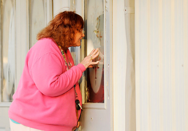 Don Knight   The Herald Bulletin<br /> Dorothy Weston peers through the windows at Cornerstone Ministries on Tuesday. Congregants say their pastor is selling the church to recoup back pay he claims he is owed.