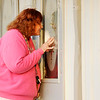 Don Knight | The Herald Bulletin<br /> Dorothy Weston peers through the windows at Cornerstone Ministries on Tuesday. Congregants say their pastor is selling the church to recoup back pay he claims he is owed.