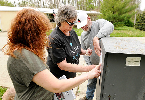 Don Knight | The Herald Bulletin<br /> From left, Shannon Cannon and Becky and Wayne Clark post a flyer as they search for Serenity Cannon and her friend Phoenix Reed who went missing from Hollywood Estates in Anderson on Thursday.