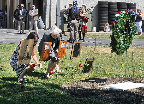 John P. Cleary   The Herald Bulletin<br /> Family members of Pendleton District fallen troopers place flowers at their photographs during the annual Indiana State Police Memorial Service held Thursday.
