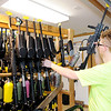 Don Knight | The Herald Bulletin<br /> Justin Harmeson pulls a paintball marker of the rack at White River Paintball on Friday.