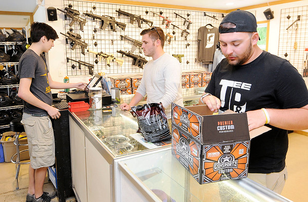 Don Knight | The Herald Bulletin<br /> Jesse Boyd rings up a paintball purchase for customers Sam Nein, center, and Charlie Lefebvre at White River Paintball on Friday.
