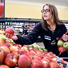 John P. Cleary | The Herald Bulletin <br /> Cross Street Pay Less associate Blair Cox sorts through the apples to pick out the ones that are blemished or discolored. They bag those separately to sell at a reduced price so the food won't go to waste.