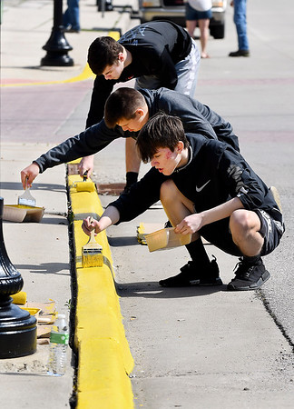 John P. Cleary | The Herald Bulletin <br /> Madison-Grant High School sophomores Lance Wilson, 16, back, Nick Evans, 16, and Max Dishman, 16, work as a team as they paint the curbs along Main Street in Summitville Wednesday morning as part of the schools Community Service Day. Teams of students were all over town doing various projects to help spruce up the area.