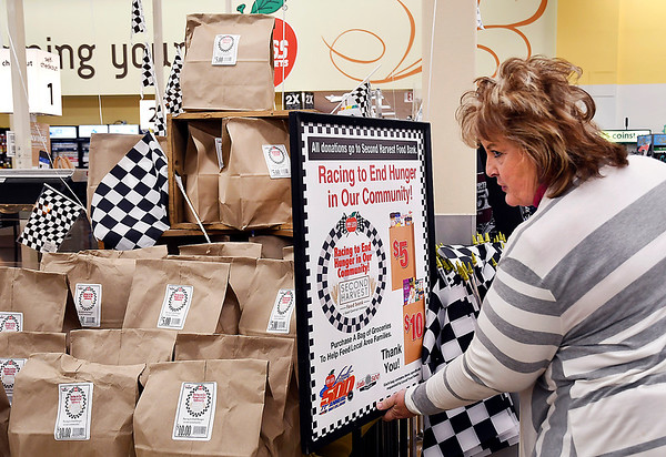 John P. Cleary   The Herald Bulletin <br /> Joyce Turner, manager of the Cross Street Pay Less Super Market, arranges the display sign for buying bags of food for the Second Harvest Food Bank display in the store.