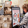 John P. Cleary | The Herald Bulletin <br /> Joyce Turner, manager of the Cross Street Pay Less Super Market, arranges the display sign for buying bags of food for the Second Harvest Food Bank display in the store.