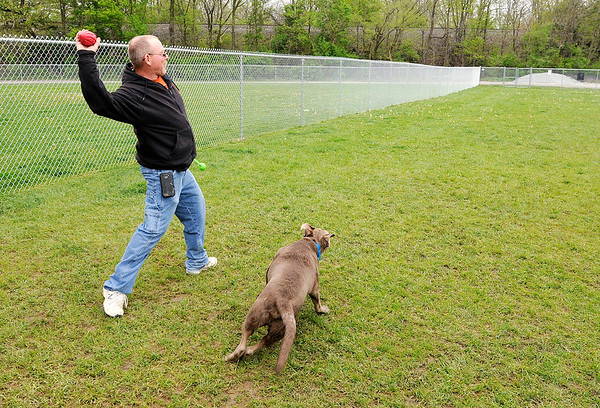 Don Knight | The Herald Bulletin<br /> Phil Braschear throws a foam football as he plays with his dog Loki at the new Falls Bark Dog Park in Pendleton.