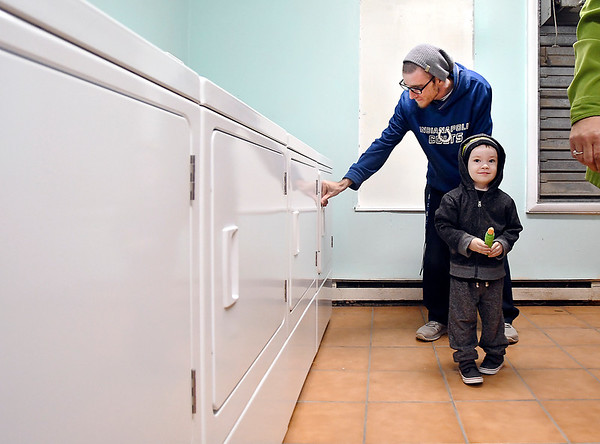 John P. Cleary | The Herald Bulletin <br /> Westvale Manor resident Derek Lloyd checks out the dryers with his son Marvin, 3, Monday as the residents got their first look at the new laundry facilities at the apartment complex. Westvale Manor has been without laundry facilities for several years.