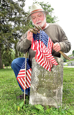 John P. Cleary   The Herald Bulletin <br /> Gerald Jones checks the number of American flags he has as he places them on each veteran's grave in West Maplewood Cemetery Wednesday.<br /> Jones inventoried the veteran graves in West Maplewood in 2003 and has taken on placing an American flag on each of the more then 200 graves each Memorial Day since then.