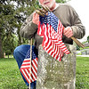 John P. Cleary | The Herald Bulletin <br /> Gerald Jones checks the number of American flags he has as he places them on each veteran's grave in West Maplewood Cemetery Wednesday.<br /> Jones inventoried the veteran graves in West Maplewood in 2003 and has taken on placing an American flag on each of the more then 200 graves each Memorial Day since then.