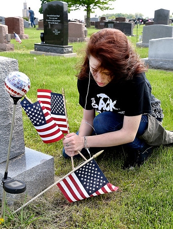 John P. Cleary   The Herald Bulletin <br /> Emily Persinger, 16, puts up a new American flag on this veteran's grave in Summitville Cemetery Thursday morning as part of Madison-Grant High School's Community Service Day.