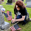 John P. Cleary | The Herald Bulletin <br /> Emily Persinger, 16, puts up a new American flag on this veteran's grave in Summitville Cemetery Thursday morning as part of Madison-Grant High School's Community Service Day.