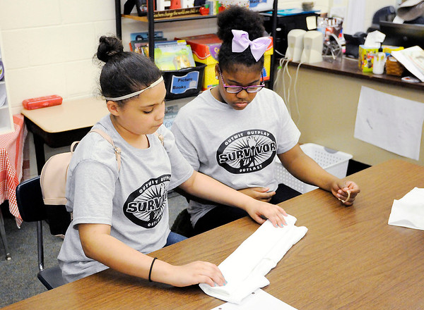 Don Knight | The Herald Bulletin<br /> From left, Natalie Robinson helps Alexis Fuller tie up a T-shirt for tie dying during a meeting of the Edge Club at Edgewood Elementary on Friday.